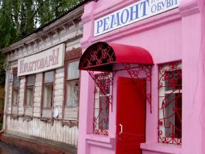 Безликие торговые павильоны наступают на бревенчатые улицы старого Александрова.
