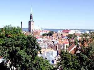 Вид, открывающийся со смотровой площадки на ул. Кохту, 12. Очертания церкви Олевисте, силуэты башен, крепостной стены, скопление черепичных крыш, а за ними бурное море.